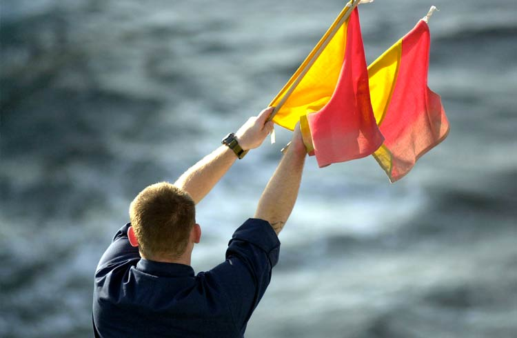 Man signaling with semaphore flags